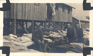 Lawrence and two friends, French and Rieves, in the midst of cleaning their barracks.