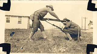 Two of Lawrence's fellow soldiers, White and Aseltine, demonstrate close quarters combat techniques.